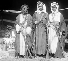 Portrait of three armed bedouin men, one with a Martini Henry rifle, one with a saif sword. - circa pre 1946.