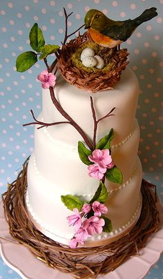 Wedding bird and nest atop 3 tiered cake with tree branch and pink flowers gracing front of cake