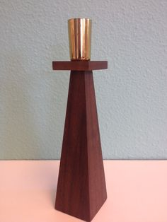 A perfect decorating accent in your atomic ranch home! This is an angular carved wood candle holder in walnut and brass, felt on the base to