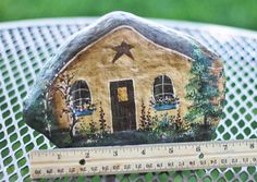 Hand painted gold rock cottage. Perfect for any Gnome or Fairy Garden. The details cover the front and back of the rock. Flowers, trees and a
