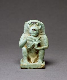 Statue of Thoth, ancient Egyptian deity of writing and knowledge, in the form of a baboon, holding an udjat-eye (aka the Eye of Horus).  Made of faience with a light green glaze.  Artist unknown; Late Period (664-332 BCE).