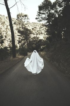 Human in ghost suit levitating on countr.