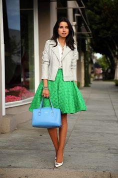 Chica usando una falda color verde y una chaqueta de piel en color blanco