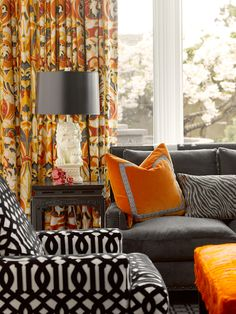 living rooms - orange gray drapes white foo dog lamps black Chinese altar end table charcoal gray velvet sofa French brass tacks Kelly Wearstler imperial trellis accent chair orange ottoman