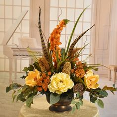 Freshen up your home with this lovely silk floral centerpiece accented with feathers. Created with warm tones of butter and rust bells of ireland, peonies, pods, magnolias foliage and grasses. Table Centerpieces For Home, Floral Centerpieces, Fall Flowers, Fresh Flowers, Fall Floral Arrangements, Pumpkin Flower, Magnolias, Grasses, Flower Pots