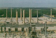 Ruinas de la Apadana del Palacio de Persépolis (S. V a.C.). La sala de audiencias constituía una apadana o sala hipóstila muy parecida a la del Palacio de Ciro II en Pasagarda. Tenía 3 pórticos monumentales a los que se accedía mediante unas esclaeras de doble rampa decoradas con relieves. Su techo de madera se aguantaba por 36 columnas distribuidas en 6 filas. Sus capiteles tenían forma de grifos, leones y toros.