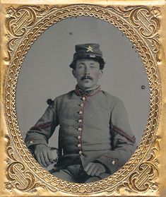 """Outstanding sixth plate ambrotype of Confederate corporal of artillery. This thing is absolutely beautiful! He sits dressed in a grey frock with red piping and matching grey trousers. Great color to this image. The chevrons have been tinted red as well. He also sports a grey cap with artillery insignia pinned to the front and company letter """"A""""."""