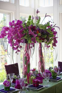 This arrangement could be made in low vases which sat directly on the table top. Phalenopsis orchids drape nicely. Bells of Ireland upright form. These could be made in any size to manage costs, this is very large.