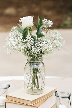 The reception centerpieces featured white roses and baby's breath in mason jars. Photo by J. Masciana Photography Flowers by Simply Beautiful Flowers & Events