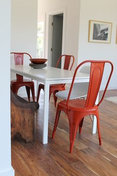 IKEA's MELLTORP table and paired it with red Tolix chairs and an Eames molded plastic dowel-leg chair.