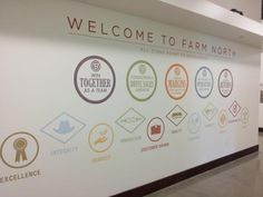 "A wall next to the employee entrance welcomes staff to ""Farm North"" and reminds them of the company's goals and values."