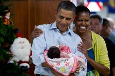The president holds 1 month old Adeline Valentina Hernandez Whitney as he and first lady Michelle Obama visit members of the military during Christmas at the Marine Corps Base Hawaii.