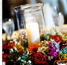 Candle in a hurricane glass surrounded by a wreath of flowers.