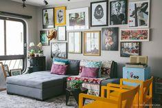 Parede cinza + cortina rolô preta + cadeiras amarelas + almofadas + frigobar retrô + milhares de molduras *---*