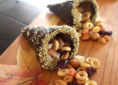 Cornucopia Snacks: 1pkg (12 count) ice cream cones,1 1/2c semi-sweet chocolate, 1 1/2c Cinnamon Burst Cheerios Cereal, 3/4c honey roasted peanuts, 3/4c mixed dried fruit (pineapple, mango, cranberries)  yellow or gold sprinkles, wax paper  * Place chocolate in microwave-safe bowl & cook at 30 second intervals, stirring after each, until melted &  smooth.