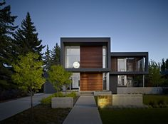 Dark grey stucco portal and wood wall. Would replace white window frame with black -  the summit | Habitat Studio