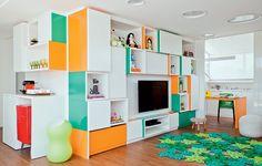 O home theater é a sala de lazer das crianças no projeto de Madá Campos. A estante colorida, composta de módulos desnivelados, agrada também aos adultos. Na base, há gavetões que organizam os brinquedos dos pequenos. O móvel se desdobra em uma bancada