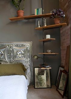 repurposed tin ceiling tile for headboard and gas pipe w/ reclaimed wood shelving