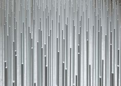 Hemp textiles are laid across metal rods in Japanese exhibition.