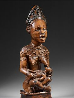 Figure: Seated Female Nursing Child Date: 19th–early 20th century Geography: Democratic Republic of the Congo; Republic of the Congo; Cabinda, Angola Culture: Kongo peoples Medium: Wood, pigments, metal Dimensions: H. 14 1/4 in. (36.2 cm), W. 4 7/8 in. (12.5 cm), D. 4 in. (10 cm)