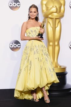 First time Oscar winner Alicia Vikander wears a yellow strapless Louis Vuitton gown designed by Nicolas Ghesquière to the 88th Annual Academy Awards. Alicia won Best Supporting Actress for her role in The Danish Girl.
