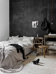 Black 'chalk board' wall with wooden furniture and neutral bedding. For contemporary #bedding and #bedroom furniture try: http://www.naturalbedcompany.co.uk/