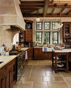 wood cabinets + black La Cornue stove + white farmhouse sink + tile flooring…