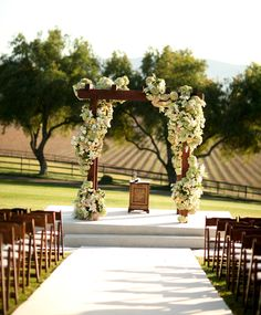 Voluptuous cascade of white and cream flowers twining around this ceremony arch.