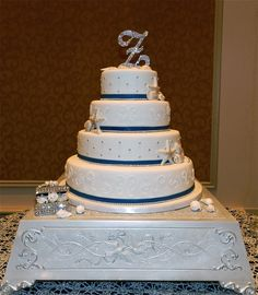 4 tier White Elegant Beach Wedding Cake - 4 tier White Wedding Cake in Butterscotch Rum flavor. Navy blue fondant band & diamond band around each tier. Silver piped dots and white hand piped design. Seashells in corner of tiers.