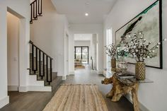A rag rug and reclaimed wood console table add texture in the foyer, leaping out from the white walls and gray floor.