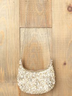 """Beautiful woven crossbody bag with pearl and bead embellishments. Metallic threading throughout body of bag. Long chain. Zipper closure. Inside fully lined.     This little pearl bag was designed exclusively for Free People with both practicality and sophistication in mind. Wear it across your chest to keep your hands free or hold it as a clutch to flaunt this party season's favorite accessory.    *By Mary Frances   *Import   *8"""" long, 7"""" deep, 1"""" wide   *25"""" strap rise"""