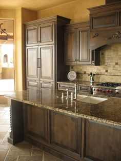 Dark stained kitchen cabinets. Like the backsplash. Great countertops!
