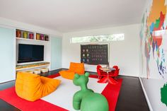 This contemporary boy's room has a beautiful red border rug topped with two orange chairs, Togo Fireside Chairs, at both ends of the rug facing each other of the rug.