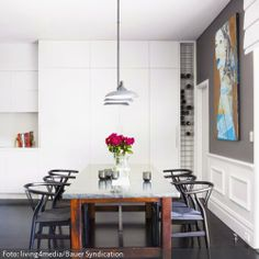 """Schwarze """"Wishbone Chairs"""" um einen Massivholztisch mit Marmorplatte: Das Esszimmer mit Designermöbeln ist äußerst elegant. Die weiße Schrankwand lässt den wertvollen Möbeln den Vortritt."""