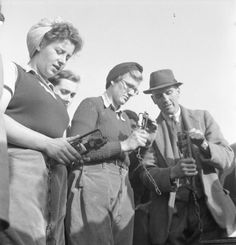 Farmer Tuppin explains the workings of a rat trap to Land Girl Margaret Wilson and her colleagues as part of their training on a Sussex farm. Margaret was a bus conductress in Yorkshire before joining the WLA. 1942