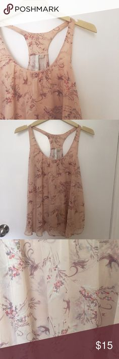 Lauren Conrad Floral Tank Nude color racer back blouse with floral and bird print. Flowy chiffon material that starts in the back and creates the drapey look seen. Size medium. Worn a few times but still like new. The third photo is the more accurate color. For some reason, the light wouldn't quite capture it. LC Lauren Conrad Tops Tank Tops
