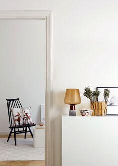 # Lampa #Leimu w kolorze miedziano-brązowy; obok #miska, a na krześle poduszka (#poszewka) z kolekcji #Tanssi
