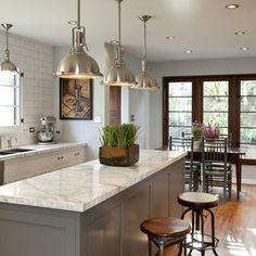 dark gray island, white cabinetry, marble, white walls, wood
