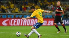 Oscar of Brazil shoots and scores his team's first goal during the 2014 FIFA World Cup Brazil Semi Final match