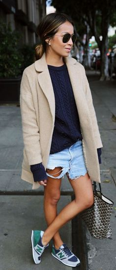 Julie Sarinana is wearing a tan wool cocoon coat from Armani Exchange, blue heavy knit blue sweater from Zara, vintage denim shorts from Levi's and the sneakers are from New Balance... | Style Inspiration