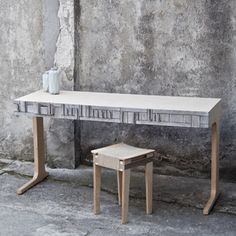 The fronts of the desk are from NewspaperWood and treated with wax. The abstracted letters are lasercut and function as the grips on the different drawers in the desk.