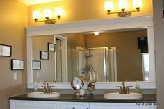 Brilliant!  placing molding around a plain builders mirror so it looks like a nice framed mirror.