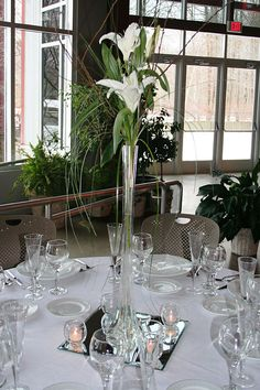 """Could not find an example of this with the Blue Dendrobium orchids, but basically, orchids or calla lillies with wisps of lily grass & maybe some gold ting ting in an Eiffel tower vase (20"""" clear or white frosted $3.50 each at flowersandsupplies.com). Venue does not allow open flame, so the votive candles at the bottom are definitely out, which eliminates the need for the mirror. Gold photo coins on top of white paper doilies would work fine."""