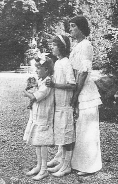 Anna Clark with her daughters Huguette (left) and Andrée (center). Huguette holds one of her dolls.