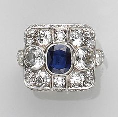 An art deco sapphire, diamond and platinum ring  of square design, centering an oval-shaped sapphire, surrounded by old-European-cut diamonds, accented by smaller European-cut diamonds on gallery and shoulders; estimated sapphire weight: 1.00 carat; estimated total diamond weight: 4.20 carats.