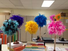 Truffula Trees made with a styrofoam ball on a plunger with a boa glued to the the ball. Easy!!
