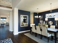 Meritage Homes Model Home Lantana - beautiful navy walls dining room with ivory dining chairs, modern chrome light fixture chandelier and dark wood floors