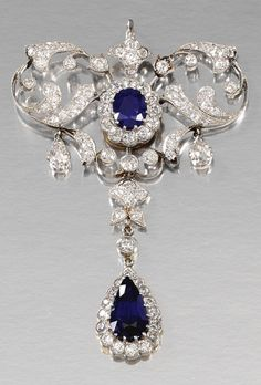 SAPPHIRE AND DIAMOND BROOCH/PENDANT, CIRCA 1910 In the Garland Style, the open work frame embellished with stylised foliate motifs millegrain-set with circular-cut diamonds and suspending two pear-shaped stones, the centre and articulated drop each designed as a cluster, the oval and pear-shaped sapphires respectively dressed by circular-cut diamonds, detachable brooch fitting, collapsible pendant fitting.