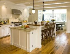 love the slab drawers, inset cabinetry, wainscoting on the island, the lower workstation and the retro pendant lighting
