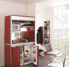 Gestion d'un petit espace optimisé avec cette cuisine compacte qui cache hotte, crédence, évier cuisinette, plaque vitrocéramique et micro-onde derrière un volet roulant le repas terminé. Dans le bas du meuble, réfrigérateur et rangement intégrés